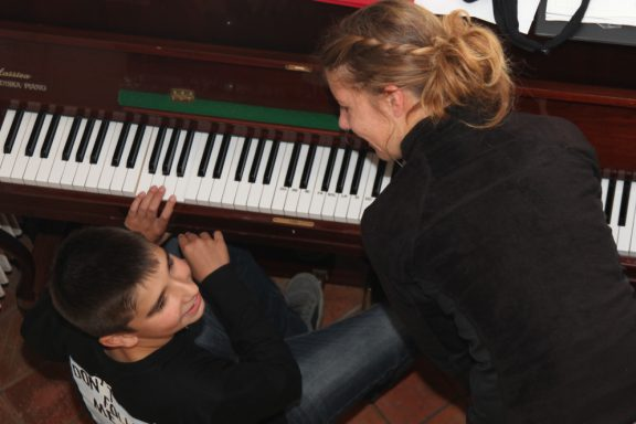 Un jeune adolescent joue du piano avec son éducatrice