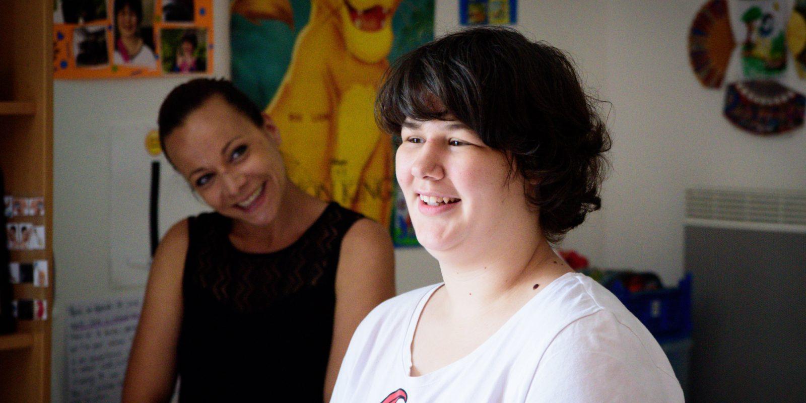 Une jeune fille et son éducatrice partagent un moment de rire