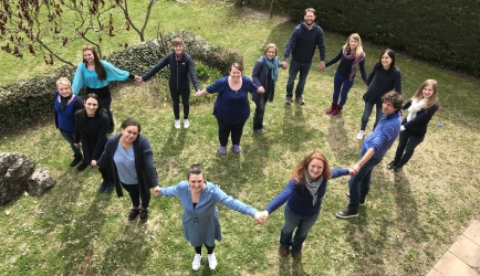 Les professionnels de l'équipe du centre OVA de Monnetier, vêtus de bleu, se tiennent la main et forment un coeur pour la journée de l'autisme