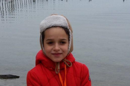 Enfant en veste rouge devant un lac