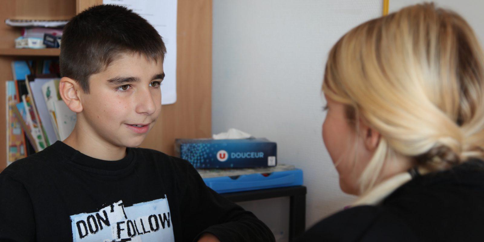 Adolescent très concentré travaillant au bureau avec son éducatrice