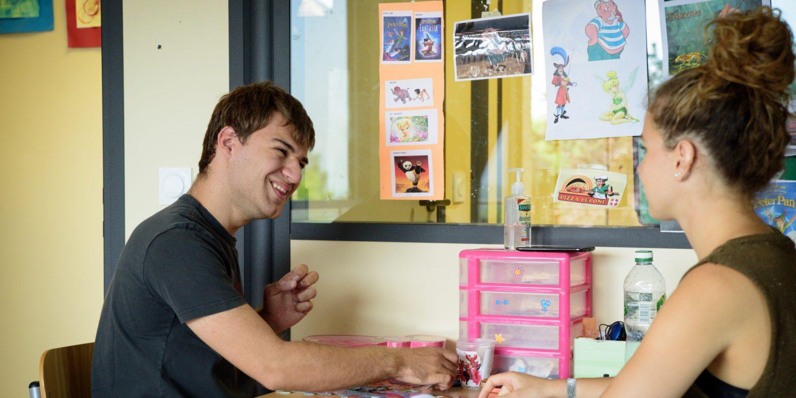 Un adolescent fait des apprentissagesà la table avec son éducatrice