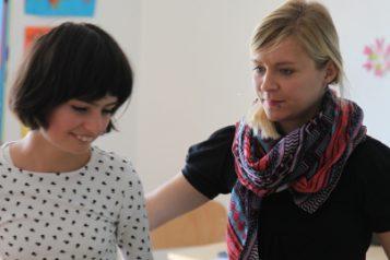 Une éducatrice dirige les pas d'une jeune fille