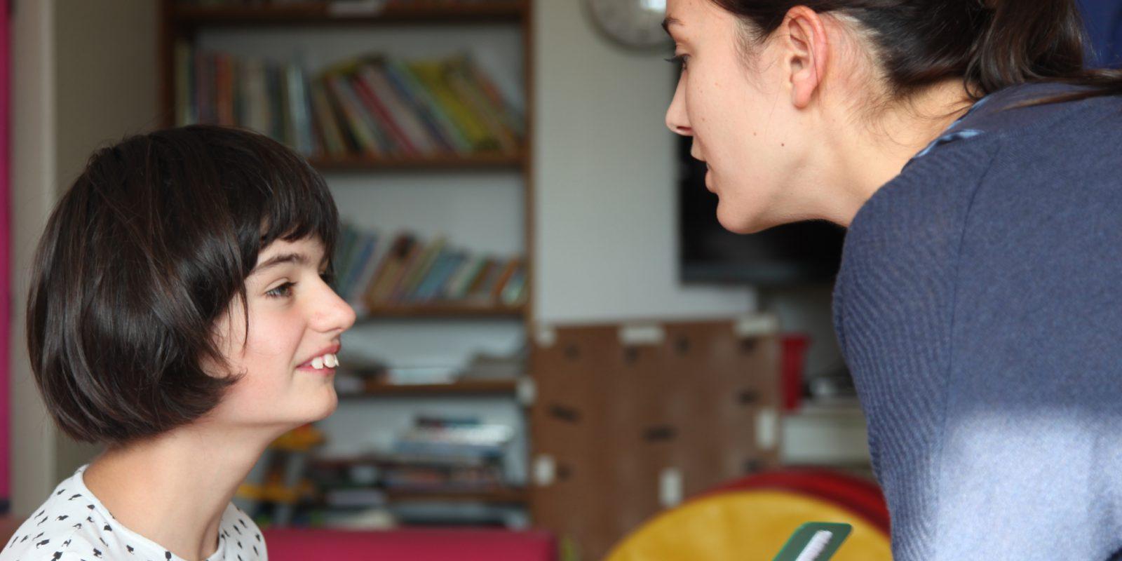 Une éducatrice montre un téléphone à une jeune fille