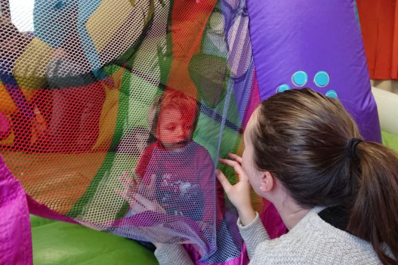 Jeu de regards entre un jeune enfant et une éducatrice à travers un filet coloré