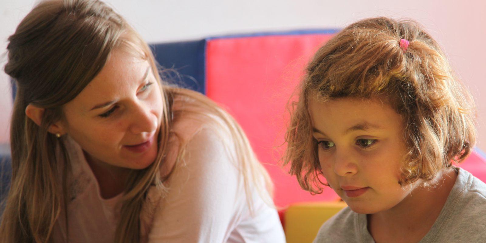 Moment d'échange entre une petite fille blonde et son éducatrice