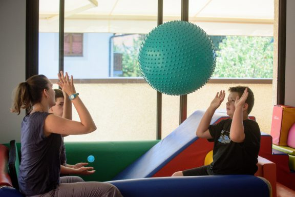 Une éducatrice lance un énorme ballon à un enfant en salle de motricité