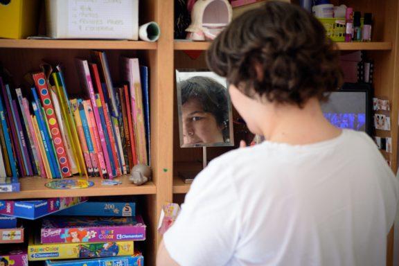 Une jeune fille regarde son reflet dans un miroir