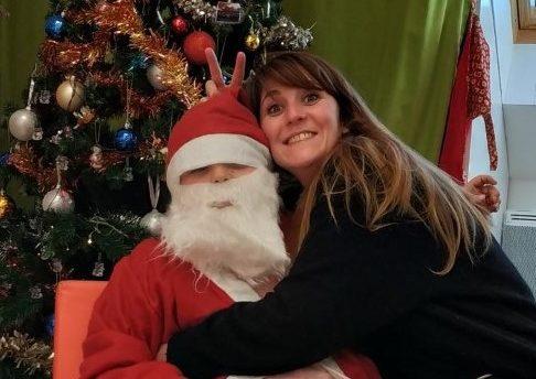 Un enfant du centre de Quintal déguisé en Père Noël et son éducatrice